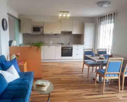 Wohnzimmer mit Küche, Essbereich sowie Couch. Balkon mit Seeblick