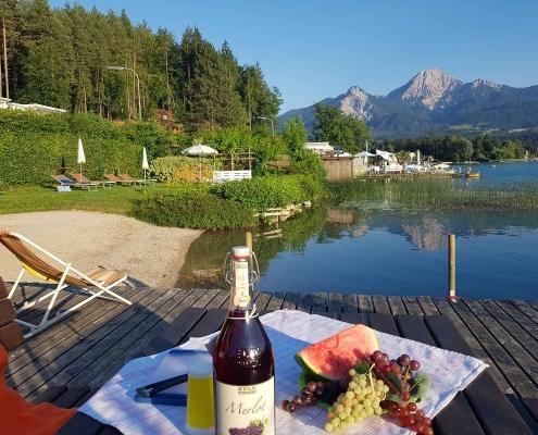 Picknick am privaten Badestrand. Traubensaft und Mittagskogel
